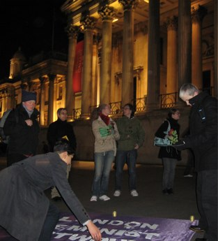 people at vigil in Trafalgar Square, arranging London Feminist Network banner on ground, photo by Sarah Barnes