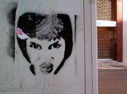 A photograph of some stencil graffiti of an angry woman. It was taken in Lisbon