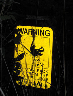A photograph of a warning sign reading Warning, stay away from the edge