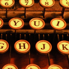 A sepia close-up image of the keys of an old-fashioned typewriter