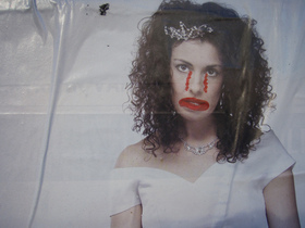 A subvertised media photograph of a woman dressed as a bride, with a sad clown's mouth and tears drawn on in red pen