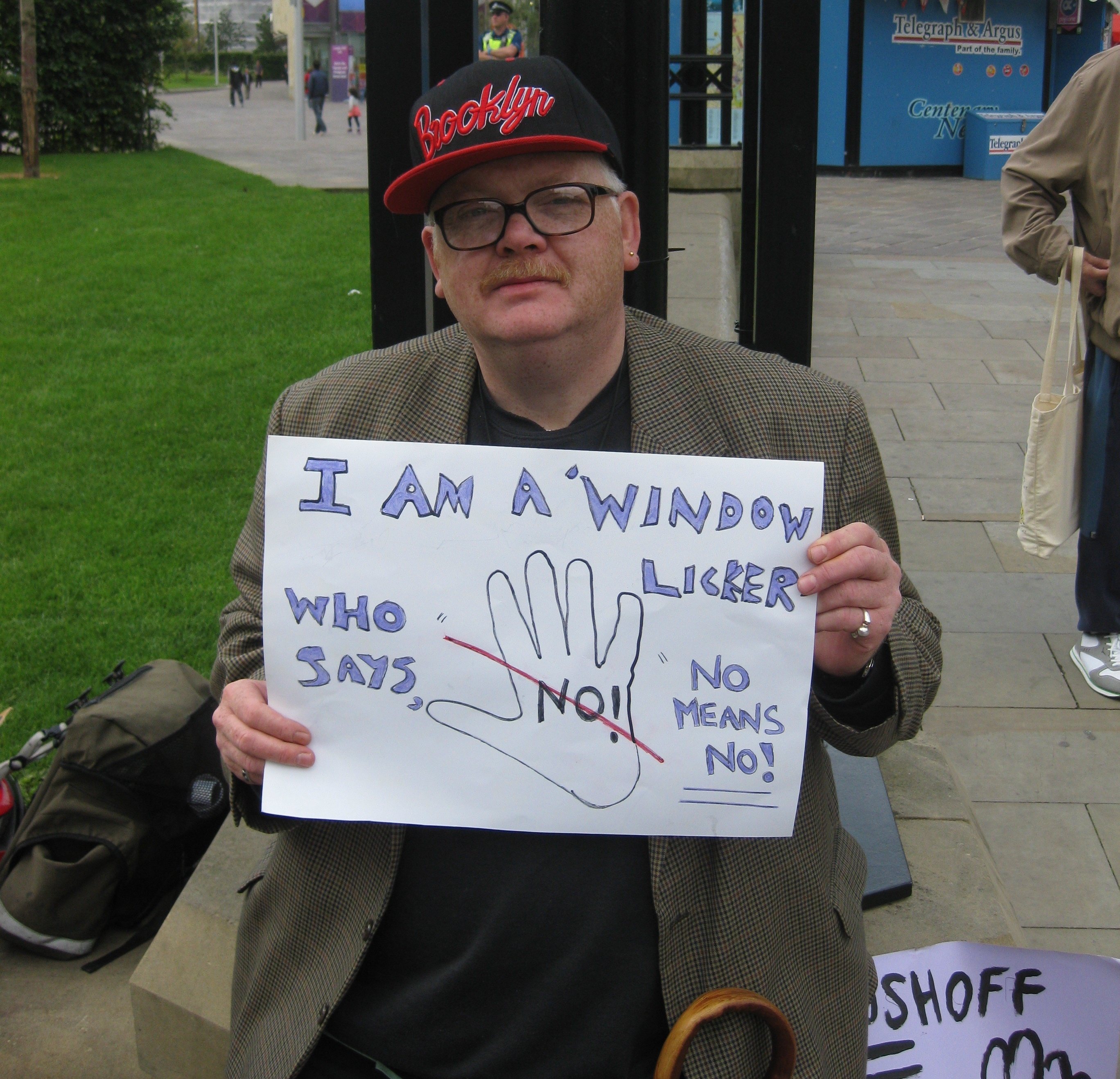 A middle-aged white man in glasses and a baseball cap holding up a handmade sign that says I'm a window licker who says no means no