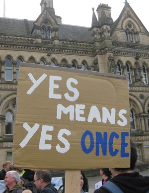 A cardboard placard held up in front of Bradford Town Hall that reads yes means yes once