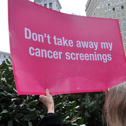 A photograph of a pink placard, which reads,