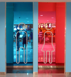A photograph of the entrance to some toilets. On the left is a blue lit door, and on the right a pink lit door. Each has a familiar male / female symbols on.