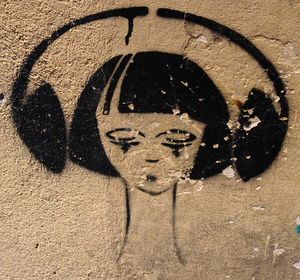 A photograph of an image of a woman wearing headphones, created with spray paint and a stencil, taken by Paul Collins in Italy.
