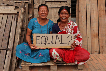 Two smiling women from Nepal, one wearing blue and the other red, holding a cardboard sign on which