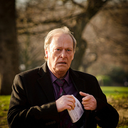 A photograph of the actor Dennis Waterman. He is in a park and wearing a black jacket and purple shirt and tie.