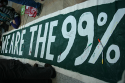 A photograph of the words We are the 99% painted in green and white on fabric on the floor. Around it are the feet and legs of various unidentified people.