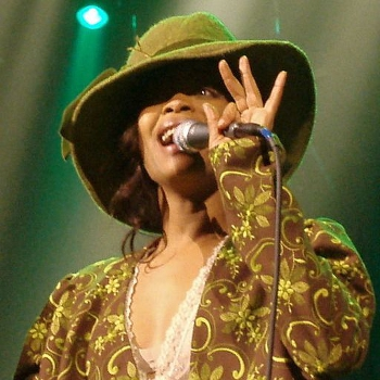 Erykah Badu performing onstage in an olive green wide brimmed hat and brown shirt with an olive green paisley-like floral design. Her left thumb and forefinger are wrapped round the microphone