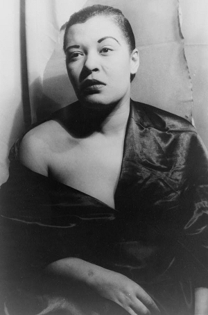 Billie Holiday looking pensive in a loose-fitting satin dress that covers her left side and hangs from her right shoulder. The shot is face-on but she is not looking directly at the camera. (Black and white.)