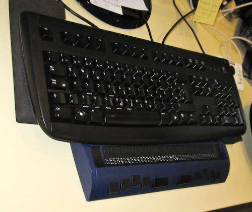 Blue and black braille keyboard in front of a standard black one