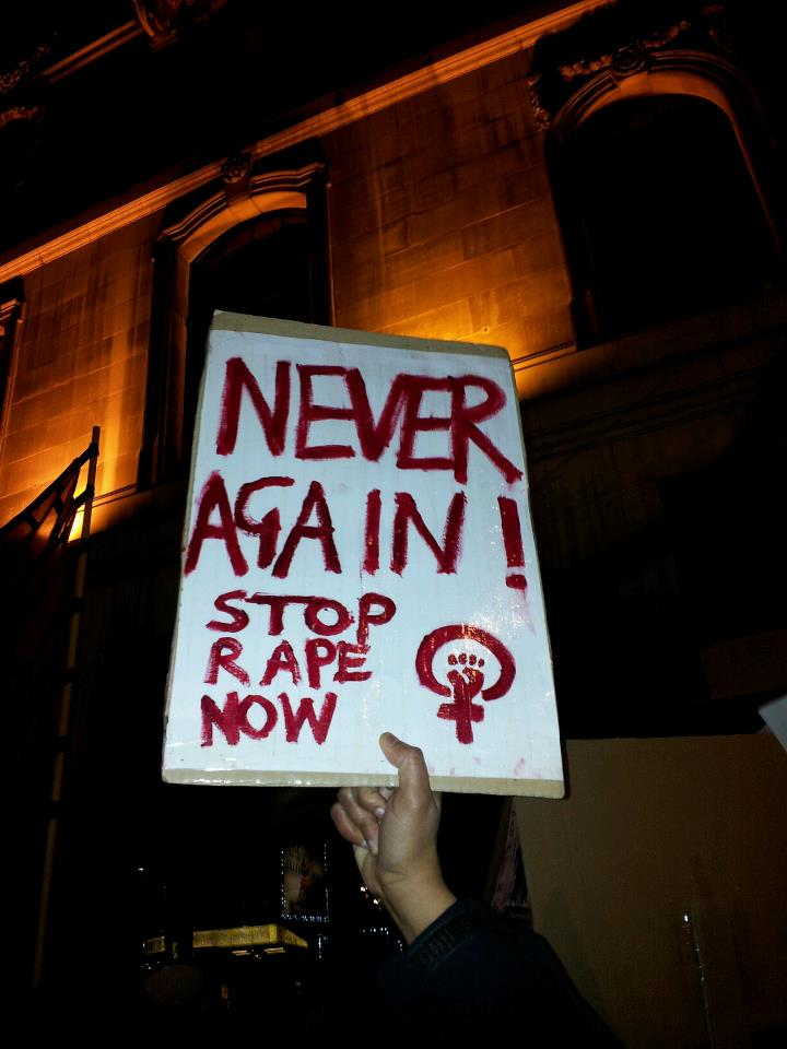Candle-light protest at Indian High Commission, London on 7 January 2013 - sign with 'Never again Stop rape now' and feminist fist.jpg