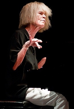 Carla Bley in black shirt and white trousers, at the piano against a black background. Her right hand is raised