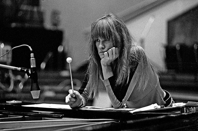 Black and white shot of a messy-haired Carla Bley intently concentrating. A percussion stick is in her right hand and she her chin is leant on her right hand