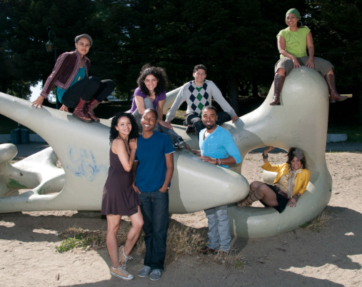 The cast of Dyke Central pose on a modernist sculpture for a publicity shot