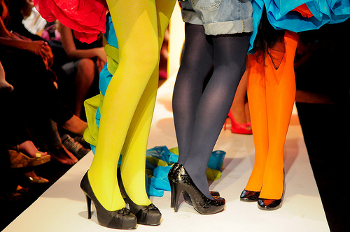 Three women on a catwalk wearing brightly coloured tights