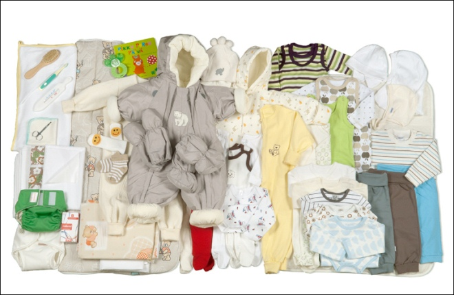 photo of the contents of the baby box: clothing of different sizes, cloth nappies, toiletries, a sleeping bag, toys, books and towels, all in yellows, browns, greens and creams