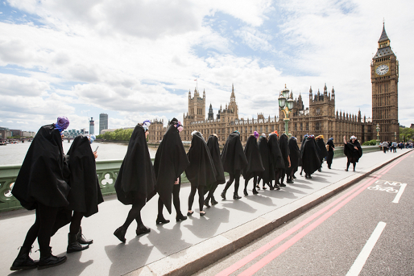 Picture named 'Boudica' showing 16 Gaggle members walking in line in black capes towards the houses of parliament in Westminster, with a leading figure turned towards them