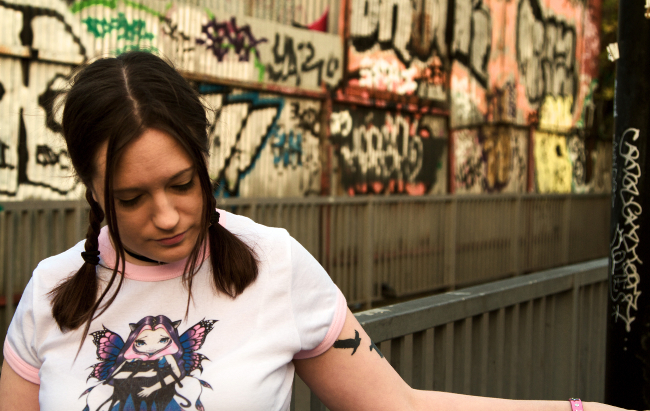Gaptooth in plaits and white T-shirt, standing in front of a wall in an urban setting, looking downwards with her left arm held out across the bottom of the picture