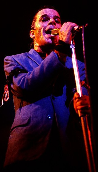 Ian Dury singing onstage with the microphone stand in his left hand and his right hand rested on the mic. His suit appears to be dark blue but this may be due to the lighting