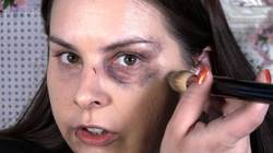 Make-up artist Lauren Luke covering up bruises around her eyes with foundation