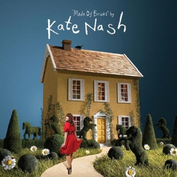 Cover of Made of Bricks (Kate Nash's first album). This shows Kate in a red dress, turning to look behind at the camera, as she walks down a winding path towards a perfectly formed quaint yellow house. There are daisies and bush sculptures (including horses rearing up) on either side of the path. Blue sky background.