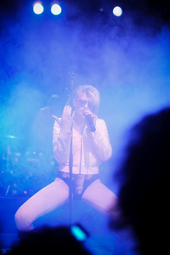 Photo of Peaches performing live, singing in front of a mic stand with her legs open. She's wearing shades, a white jacket and a black leotard. The image on the leotard is an upside down fist with the middle finger extended to point at her crotch.