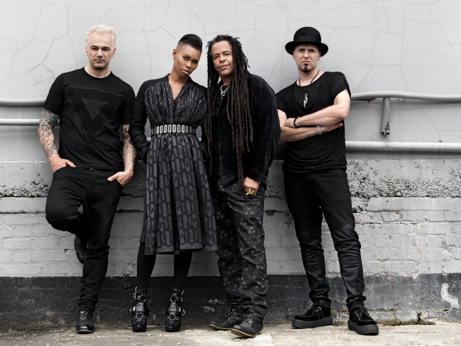 Mark, Skin, Cass and Ace (in that order) of Skunk Anansie, all wearing black and dark grey. Standing against a white wall.