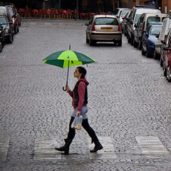 The image Walking in the Rain shows a young woman sheltering under an umbrella as she crosses a cobbled urban street