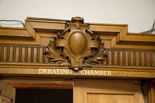 Wooden carving over the door of a debating chamber, with the words Debating Chamber.jpg