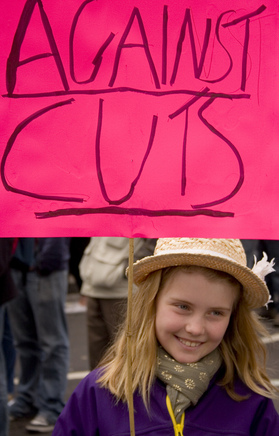 A photograph of a young blonde girl wearing a straw hat and purple coat. She is smiling and holding a bright pink handmade sign which reads