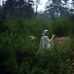 The image is a photo of a young woman wearing a grey, hooded cloak and carrying a cloth bindle (bundle) on a stick over her shoulder. She is walking into the distance of a wooded landscape but has partially turned back towards the camera so that her face is visible in profile.