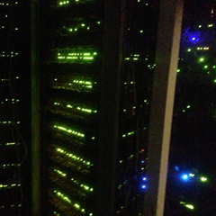 Blinkenlights - a photo of a darkened computer room illuminated by the green and blue lights of active network connectivity devices