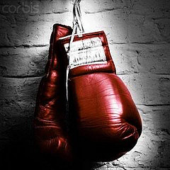 shiny red boxing gloves hanging against a white brick wall