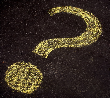 yellow question mark chalked on a tarmac road