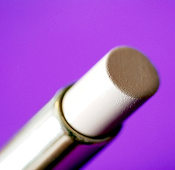pale stick of concealer on a purple background