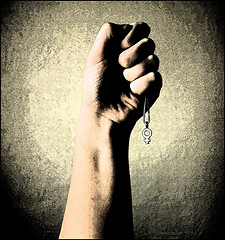 a white woman's forearm and fist holding up a necklace with the female symbol