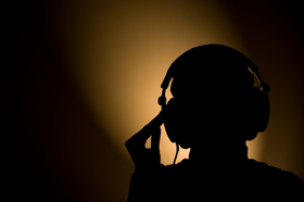 A photograph of a silhouetted person wearing headphones, against a dark gold background.