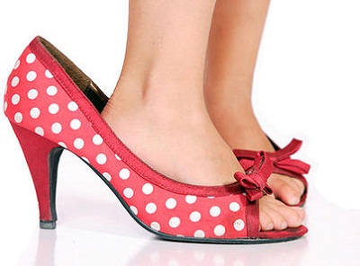 white child's feet in red high heeled shoes with white spots on