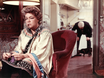 Screenshot from Le Chat, showing an older woman in the foreground smoking a cigar, and an older man in the background petting a cat