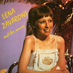 Cover of Lena and Her Music (1981). Head and shoulders shot of a seated Lena, with short hair and a white top (or dress), smiling at a possible audience rather than the camera. Tinsel/palm fixture and light purple background behind