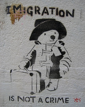 graffiti stencil of paddington bear and text reading immigration is not a crime