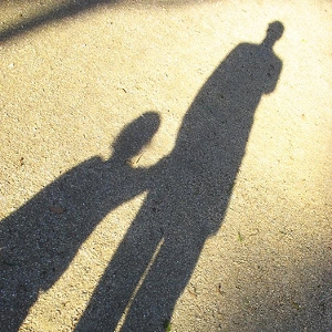 Pavement shadow of a child holding the hand of an adult on the right