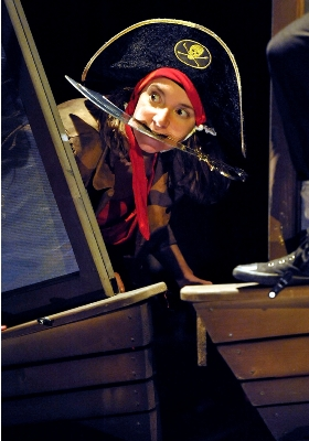 Photo of a female pirate peering round the side of a boat with a cutlass in her teeth.