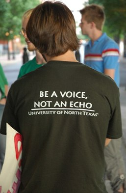 man on University of Texas violence against woman protest, wearing a shirt that says 'be a voice, not an echo