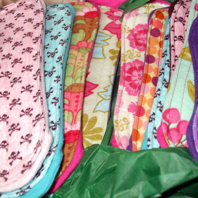 A photograph of a selection of handmade washable sanitary towels in various colours and patterns, on green tissue paper