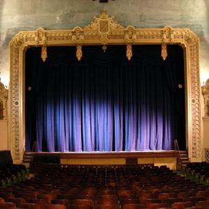 The stage of a theatre, with the curtains closed