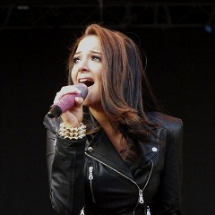 Photo of Tulisa singing into a mic onstage at a festival, wearing a black leather jacket