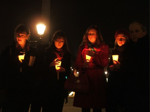 women holding candles at vigil, photo by Ange